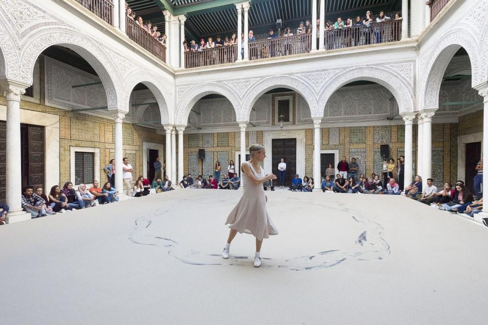 Une femme danse sur une scène installée dans une cour intérieure